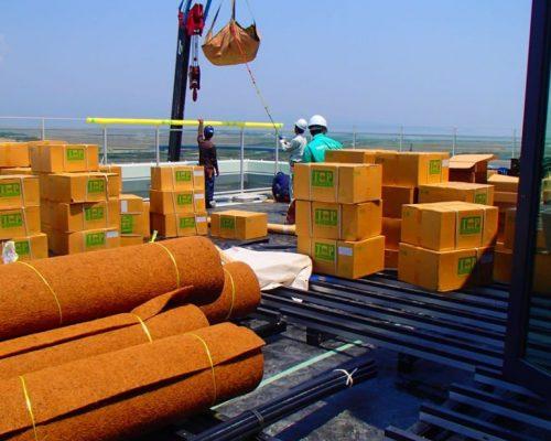 ①地上部より屋上資材の荷揚げ作業。