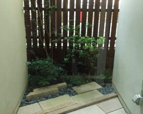 ③目地の広いウッドフェンスと日陰に耐える植物を選び手前は石張りで仕上げた坪庭です。