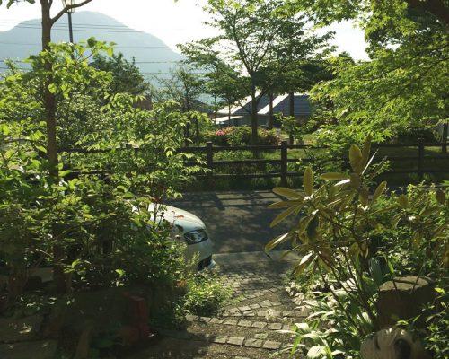 ④玄関を出た所より見た景色。(前面にある公園のサクラと、背景にある山々を一体としたスペース)